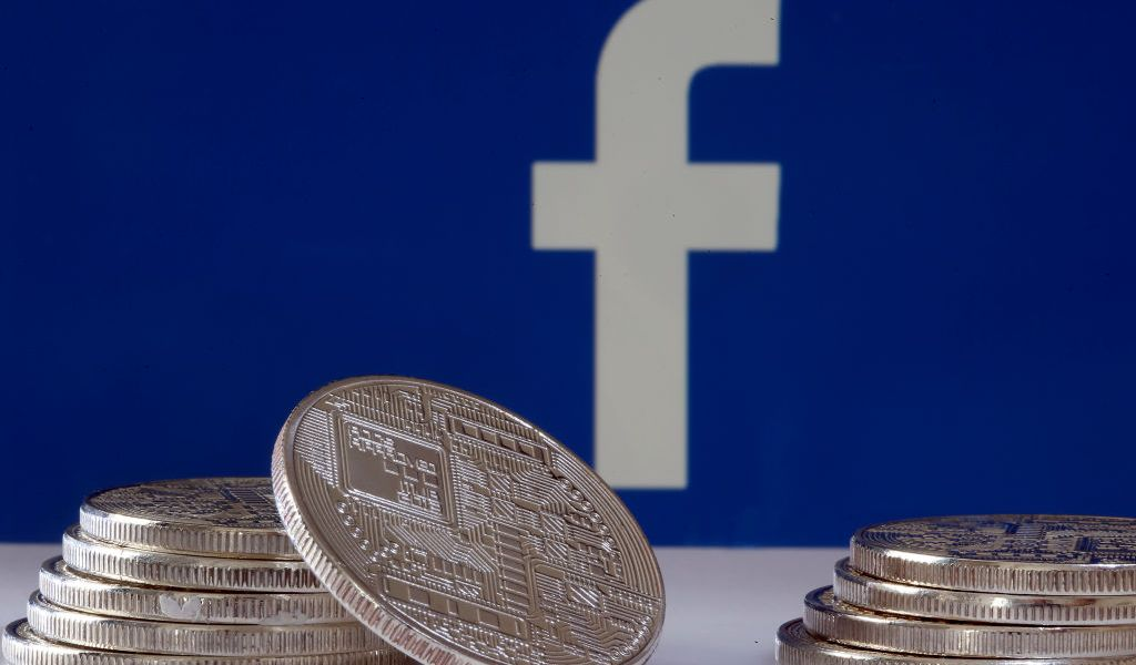 """PARIS, FRANCE - JUNE 18: In this photo illustration, a visual representation of a digital cryptocurrency coin sits on display in front of a Facebook logo on June 17, 2019 in Paris, France. Facebook will announce Tuesday, June 18 the details of its cryptocurrency, called """"Libra"""". Like bitcoin, the best-known virtual currency, it will rely on blockchain technology. This universal currency must allow its users to buy products or services from the Facebook universe, which also owns Messenger, Instagram and WhatsApp. It will also be possible to transfer """"Libras"""" between individuals. Several companies like Visa, MasterCard, PayPal and Uber have already joined the consortium created by Facebook. (Photo by Chesnot/Getty Images)"""