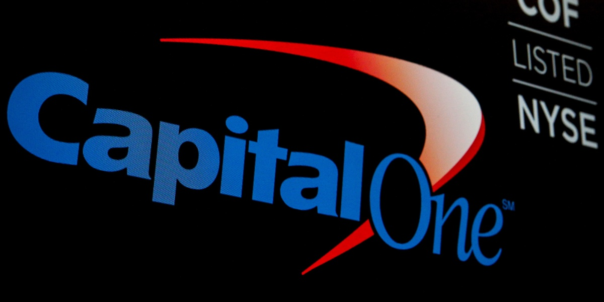 The logo and ticker for Capital One are displayed on a screen on the floor of the New York Stock Exchange (NYSE)