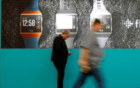 Visitors walk past an advertising billboard for Fitbit Ionic watches at the IFA Electronics Show in Berlin