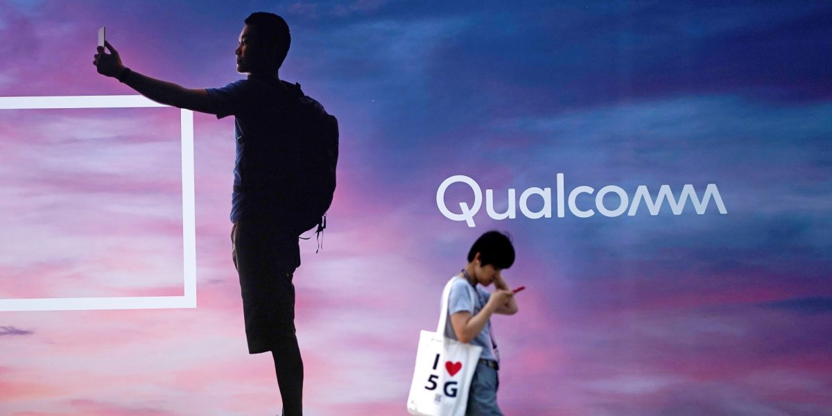 A woman walks past a sign advertising Qualcomm at Mobile World Congress (MWC) in Shanghai, China