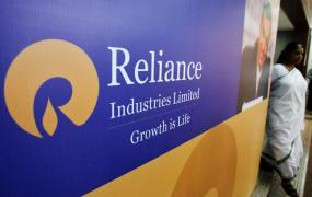 A woman walks past a poster of Reliance Industries installed outside the venue of the company's annual general meeting in Mumbai June 7, 2012.