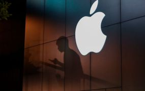 """The shadow of a man is cast on the wall of an Apple store as he uses his mobile phone in Beijing on August 26, 2019. - There were signs of a thaw in frosty trade-war tensions between China and the US on August 26 as President Donald Trump said delegations would """"very shortly"""" resume talks and Beijing's top negotiator called for """"calm"""". (Photo by GREG BAKER / AFP)        (Photo credit should read GREG BAKER/AFP/Getty Images)"""