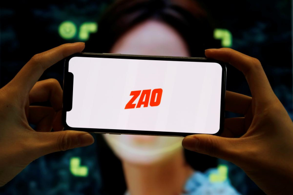 The logo of the Chinese app ZAO, which allows users to swap their faces with celebrities and anyone else, is seen on a mobile phone screen in front of an advertisement of the app, in this illustration picture taken September 2, 2019.