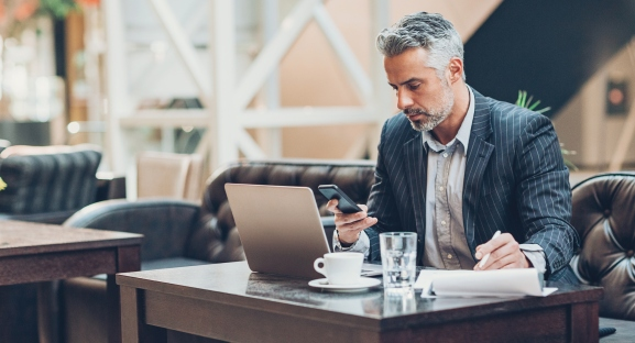 Serious businessman with laptop and documents at comfortable setting