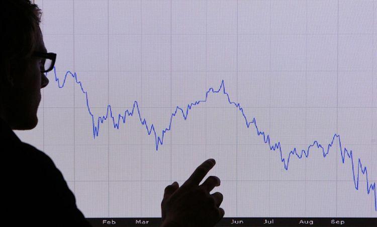 A man looks at a graph representing a 12 month financial decline.