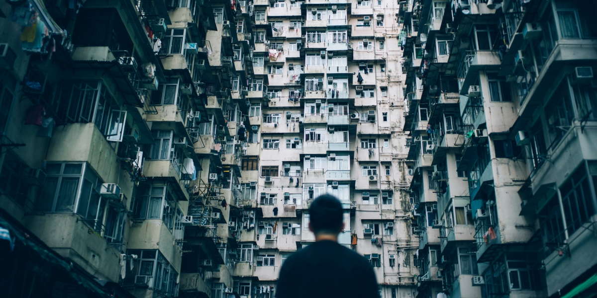 Rear view of young man surrounded by old traditional residential buildings and lost in city