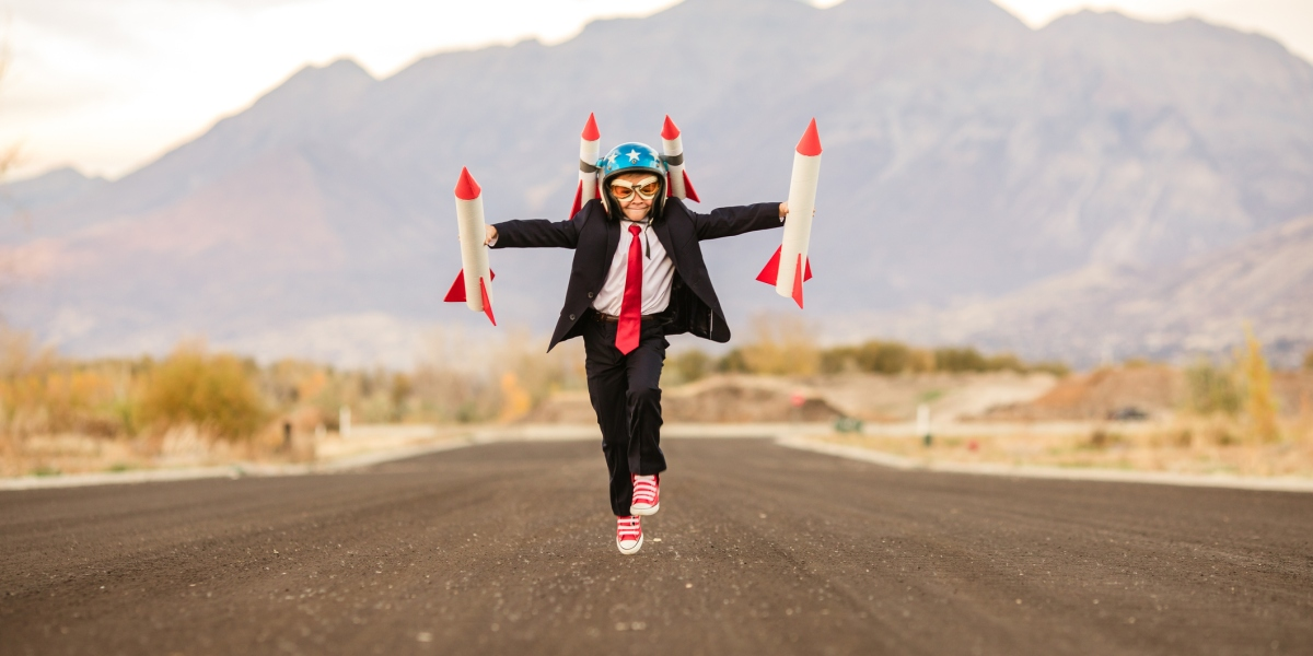 A young business boy in a rocket helmet and rockets in each hand is running for take off. He is breaking new ground as he launches his new ideas. His dream is to establish his own small business. This photograph was taken in Utah, USA.