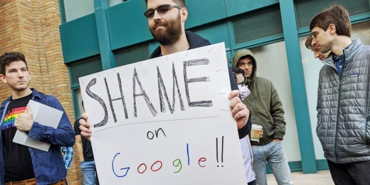 Adam Campbell holds a protest sign that reads Shame on Google
