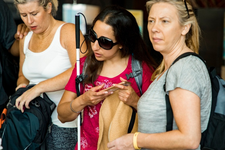 A blind woman with dark glasses and a walking stick tilts her head to hear her smartphone.