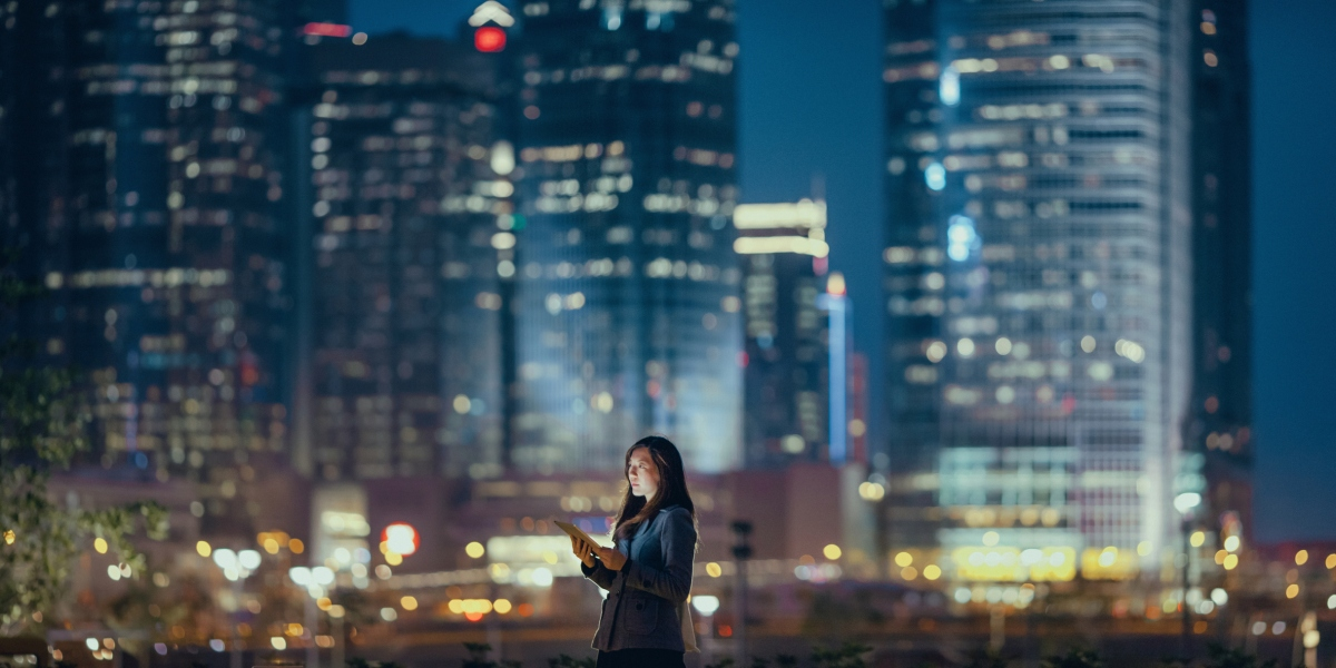 Young businesswoman using digital tablet in financial district, against illuminated corporate skyscrapers at night