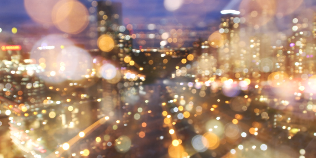 Blurred city lights at dusk, indicate speed and direction