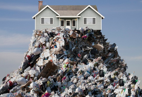 A brand new house is perched on top of a mountain of garbage