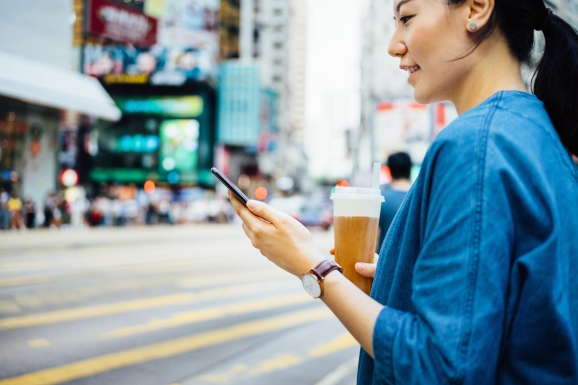 On a city street, a woman looks at her smartphone