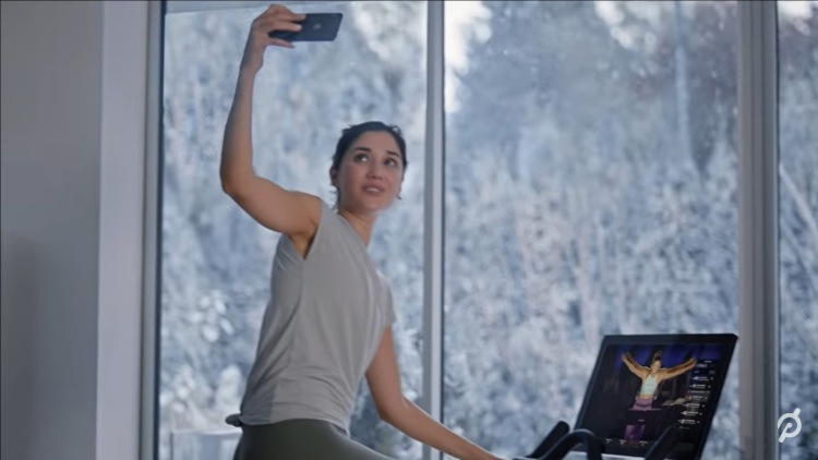 Still frame from Peloton video showing young woman on exercise bike