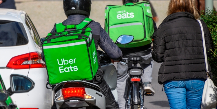 LISBON, PORTUGAL - NOVEMBER 21: Uber Eats drivers ride a scooter and a bicycle near Praça Marques de Pombal on November 21, 2019 in Lisbon, Portugal.