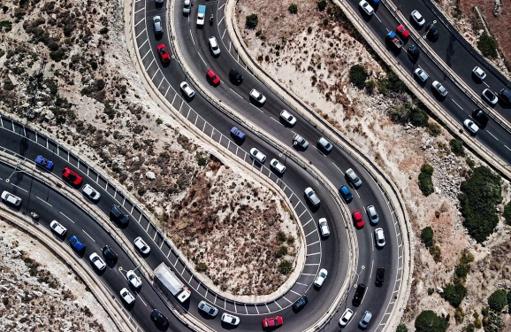 Aerial view of cars on winding road shaped as letter S