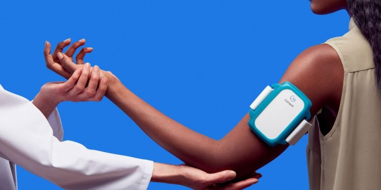 One person adjusts the arm position of a second person wearing a Current Health health-monitoring armband