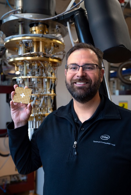 "Jim Clarke, Intel Corporation's director of quantum hardware, holds an Intel 49-qubit quantum test chip, called ""Tangle Lake,"" in front of a dilution refrigerator at QuTech's quantum computing lab inside Delft University of Technology in July 2018. QuTech at Delft University of Technology is Intel Corporation's quantum computing research partner in the Netherlands."