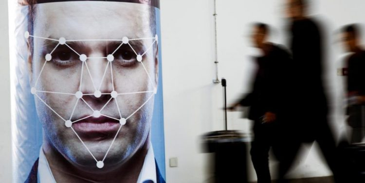 People walk past a poster simulating facial recognition software at the Security China 2018 exhibition on public safety and security in Beijing, China October 24, 2018.