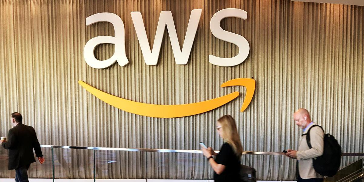 Attendees at Amazon's annual cloud computing conference walk past the AWS logo