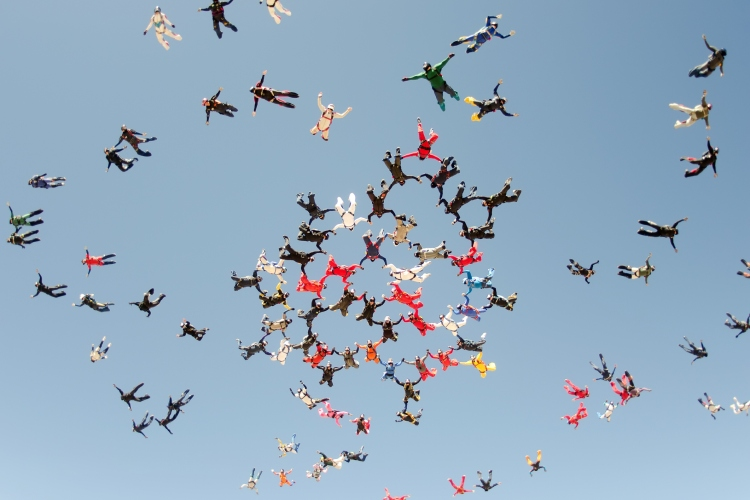 a scattered group of sky divers in different colors begin to form a group mid-air