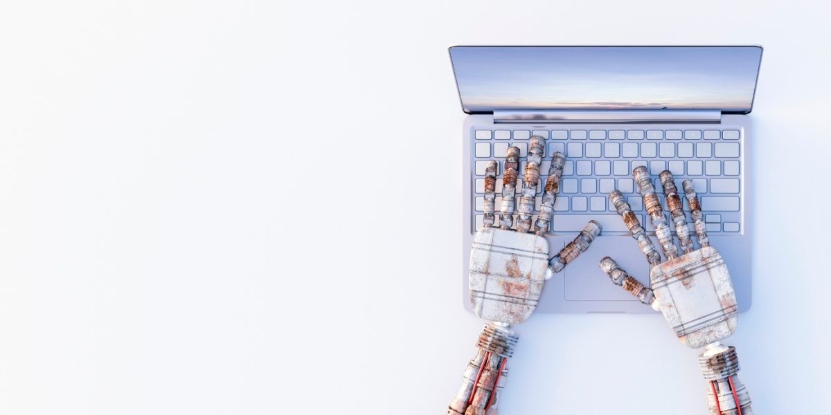 Robot hands typing on a laptop