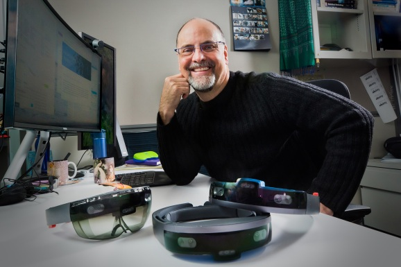 Ed Cutrell, a senior principal researcher with Microsoft's research organization, sits behind several modified HoloLens units used by Project Tokyo researchers.