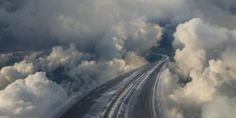 An empty highway curves off into clouds
