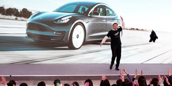 Tesla CEO Elon Musk takes off his coat onstage during a delivery event for Tesla China