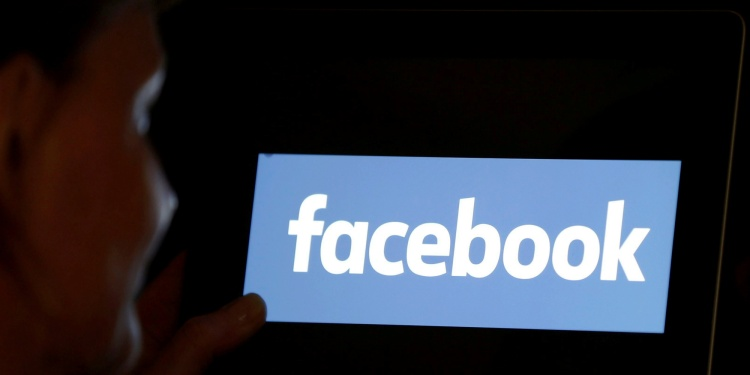 A woman looks at the Facebook logo on a screen, June 3, 2018.