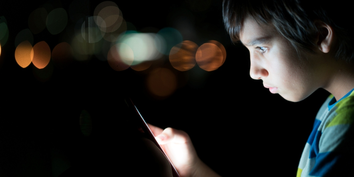 Child's face illuminated by a digital screen