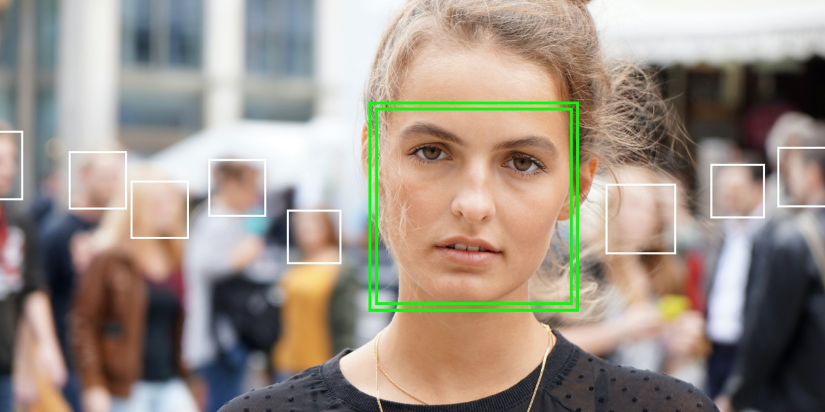 young woman picked out by face detection or facial recognition software - several other faces detected in crowd of people in background (young woman picked out by face detection or facial recognition software - several other faces detected in crowd of