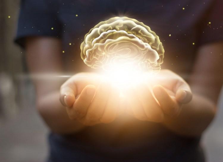hands hold a bright, virtual brain