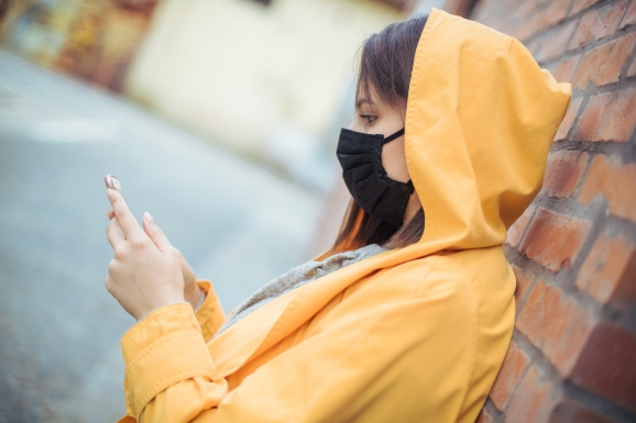 A young woman stares at her phone while wearing a face mask in a polluted city
