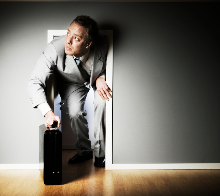 Businessman trying to fit through a very small door.