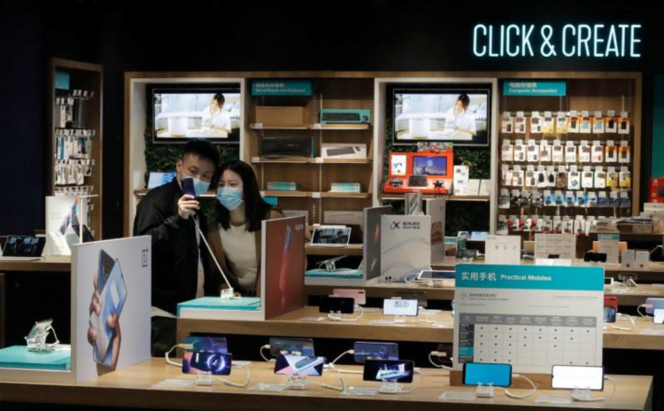 People wearing protective masks look at phones at an electronic retailer in Beijing, China March 25, 2020.