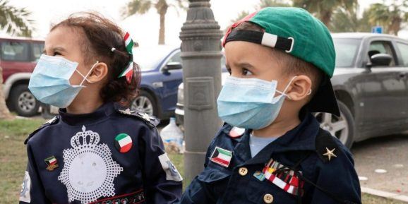 Kuwaiti kids wear protective face masks, following the outbreak of coronavirus, during celebrations of the 29th Kuwait Liberation Day from the Iraqi occupation, in Kuwait on February 26, 2020.