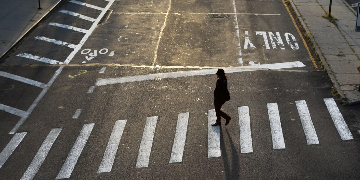 A woman crossing an empty street in Dumbo, Brooklyn, New York City, USA