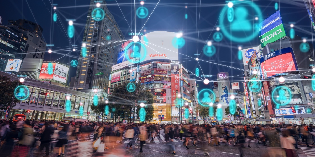 A busy street scene at night with digital personalization symbols above passersby