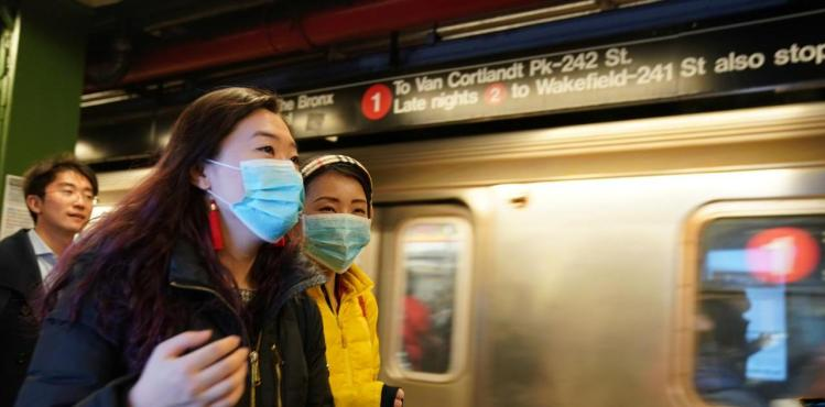 FILE PHOTO: People wear surgical masks in the subway station at Times Square in New York, U.S., January 31, 2020.
