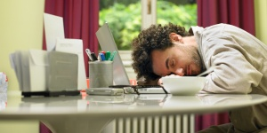 Man at breakfast table asleep on laptop computer, side view