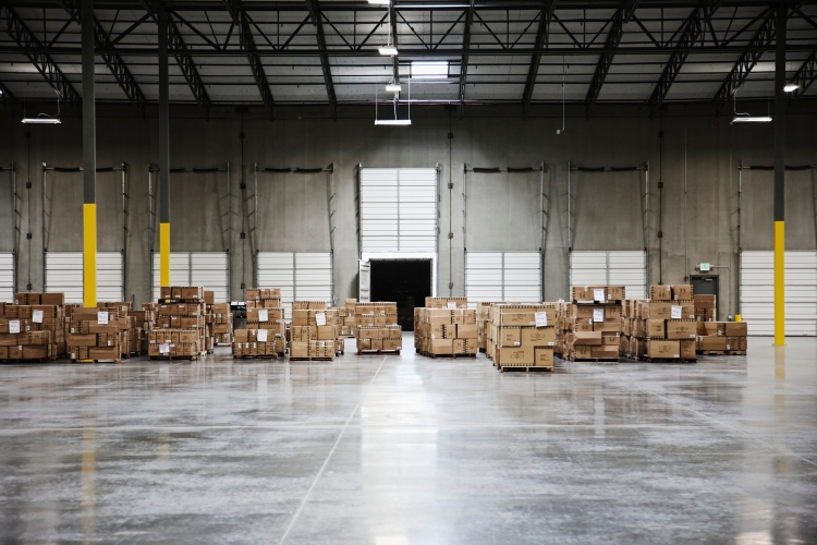 A few stacks of boxes sit in a mostly empty warehouse
