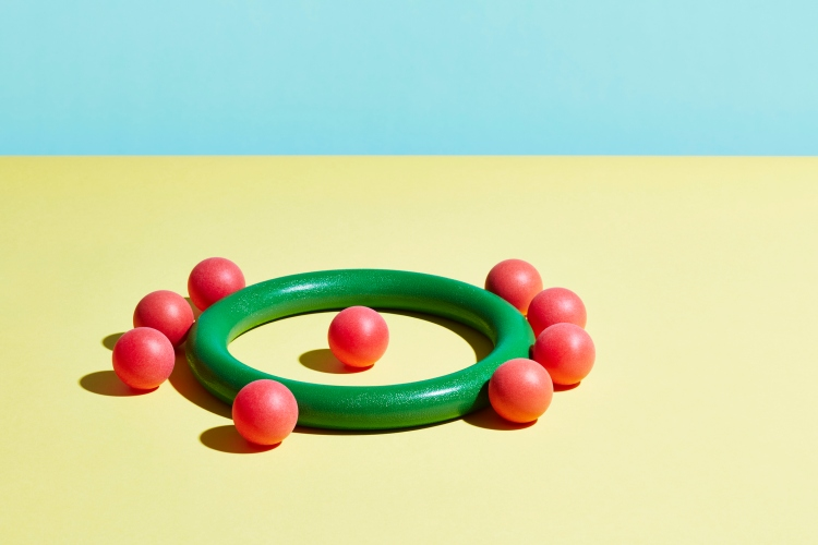 A single red sphere sits inside a green hoop surrounded by red spheres