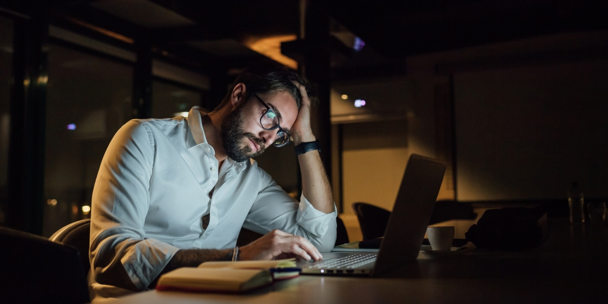 Stressed businessman in office at night working on laptop