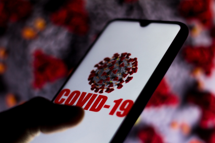 In this photo illustration the Covid-19 virus is displayed on the smartphone screen.
