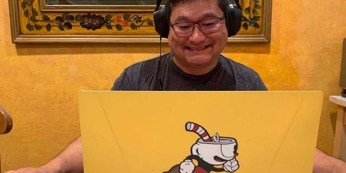 Dean Takahashi plays on a Cuphead-covered Origin PC laptop.