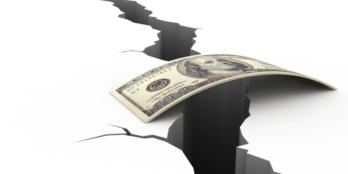 A 100 dollar bill forms a bridge over a chasm