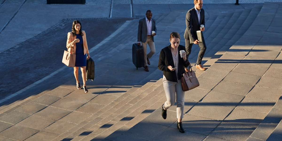 Businesspeople walking with bags on staircase outside, at sunrise