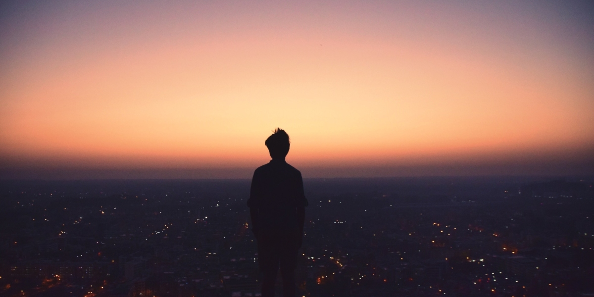 silhouette of a person on a hill top at dawn looking out over a city