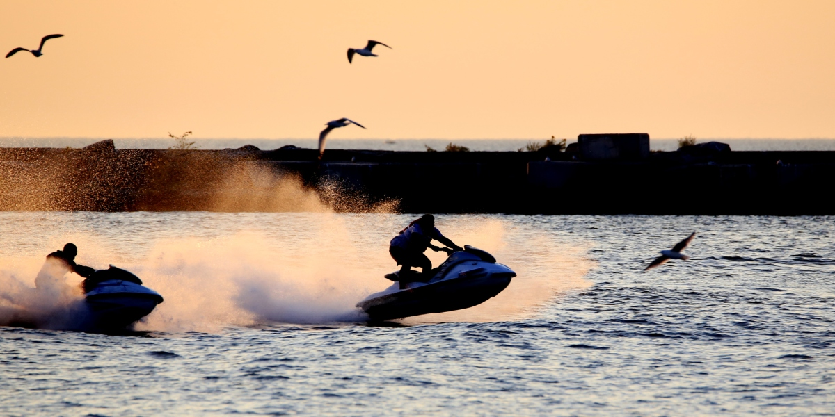 Silhouette of jet ski riders heading out to ocean at dawn